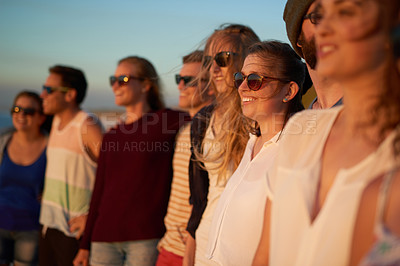 Buy stock photo Cropped shot of a young woman standing next to her friends at the beach