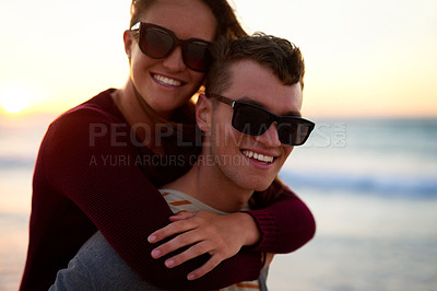 Buy stock photo Closeup portrait of a young man piggybacking his girlfriend at the beach