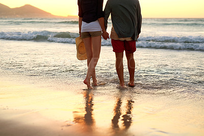Buy stock photo Cropped shot of an unidentifiable couple taking a walk while holding hands at the beach