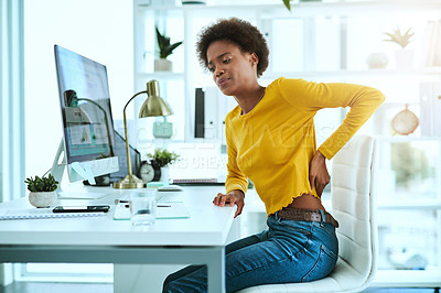 Buy stock photo Shot of a young businesswoman suffering with back pain while working in an office