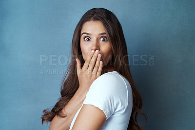 Buy stock photo Studio shot of an attractive young woman looking surprised a blue background