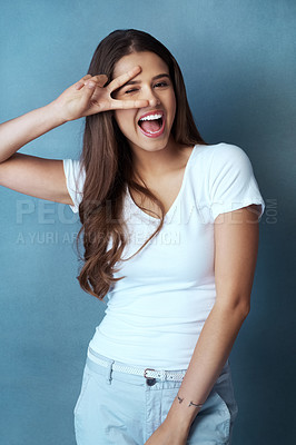 Buy stock photo Studio shot of an attractive young woman looking through her fingers against a blue background