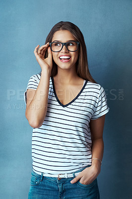 Buy stock photo Studio shot of an attractive young woman looking thoughtful against a blue background