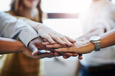Buy stock photo Cropped shot of a group of unrecognizable colleagues joining their hands in solidarity at work