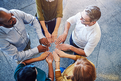 Buy stock photo High angle shot of a group of colleagues joining their hands in solidarity at work