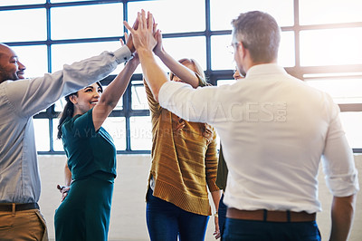 Buy stock photo Cropped shot of a group of colleagues giving each other a high five in a modern office