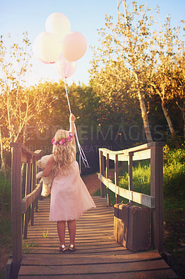 Buy stock photo Shot of an unrecognizable little girl holding balloons and a teddy bear while standing in the middle of a bridge