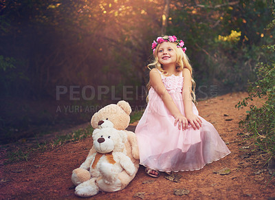 Buy stock photo Shot of a happy little girl sitting and waiting with her teddy bears in the middle of a dirt road
