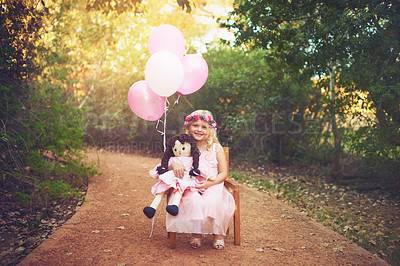 Buy stock photo Shot of a happy little girl sitting and waiting with a doll and balloons in the middle of a dirt road