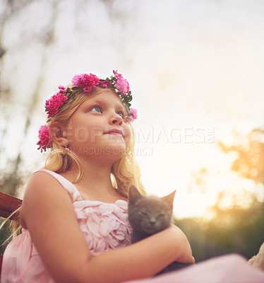 Buy stock photo Shot of a little girl holding a kitten and looking into the distance while standing outside in nature