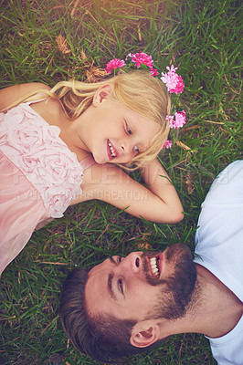 Buy stock photo Shot of a happy daughter and father lying on the ground looking at one another outside in nature