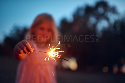 Buy stock photo Shot of an unrecognizable little girl playing with a sparkler at night time outside in nature
