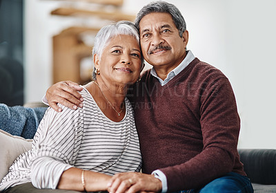 Buy stock photo Cropped shot of a cheerful elderly couple seated on a couch together while holding each other at home during the day