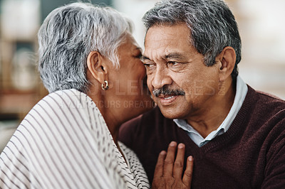 Buy stock photo Cropped shot of an elderly couple seated on a couch together while whispering in each other's other's ears at home during the day
