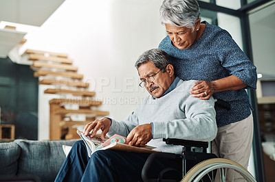 Buy stock photo Cropped shot of a cheerful elderly woman pushing her husband around in a wheelchair while he reads the newspaper at home during the day