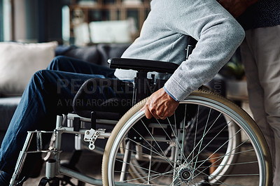 Buy stock photo Low angle shot of an elderly man moving in his wheelchair  at home during the day