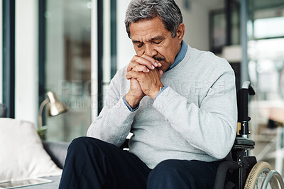 Buy stock photo Shot of a relaxed elderly man seated in a wheelchair while praying at home during the day