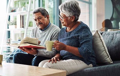 Buy stock photo Cropped shot of a relaxed elderly couple reading from the bible while drinking coffee at home during the day