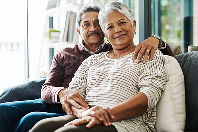 Buy stock photo Portrait of a cheerful elderly couple seated on a couch together while holding each other at home during the day