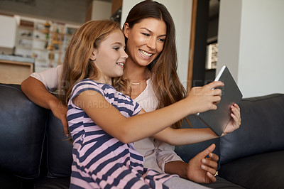 Buy stock photo Shot of a little girl and her mother using a digital tablet together at home