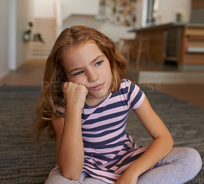 Buy stock photo Shot of a little girl looking bored at home
