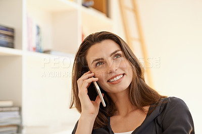 Buy stock photo Shot of a young woman using a smartphone while working from home