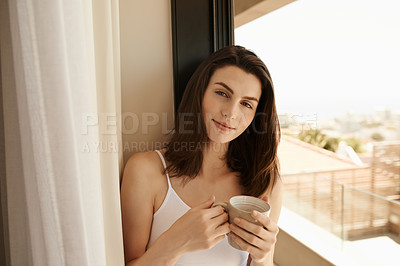 Buy stock photo Shot of a beautiful young woman having her morning coffee at home