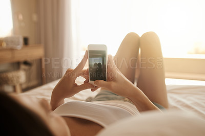 Buy stock photo Shot of a young woman lying in bed and taking pictures on her smartphone in the morning