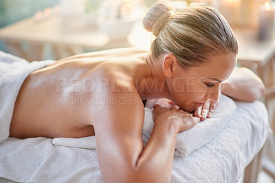 Buy stock photo Shot of a mature woman relaxing on a massage table at a spa