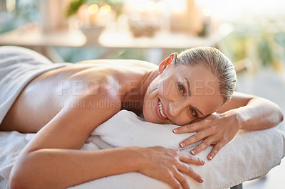 Buy stock photo Portrait of a mature woman relaxing on a massage table at a spa