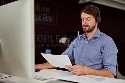 Buy stock photo Shot of a call center agent holding a document while on a call