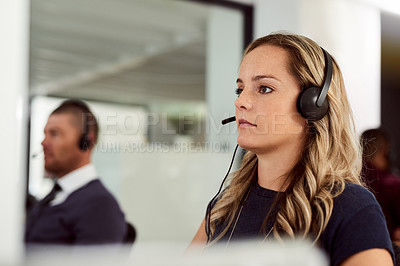 Buy stock photo Shot of a call center agent working in an office with colleagues sitting in the background