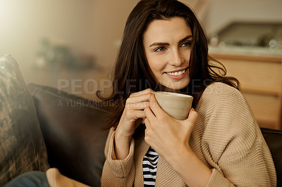 Buy stock photo Shot of a beautiful young woman relaxing with a cup of coffee at home