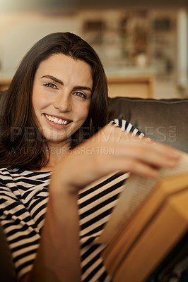 Buy stock photo Portrait of a beautiful young woman reading a book at home