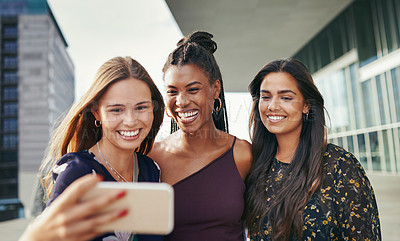 Buy stock photo Shot of a group of young women taking selfies together outside on campus