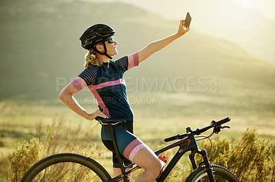 Buy stock photo Shot of a sporty woman taking a selfie while out cycling