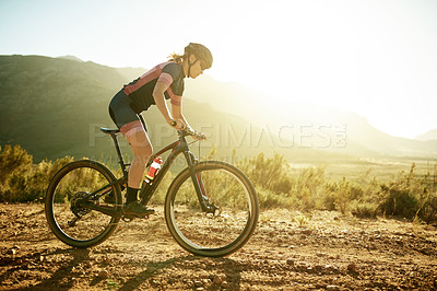 Buy stock photo Shot of a sporty young woman out cycling in the countryside
