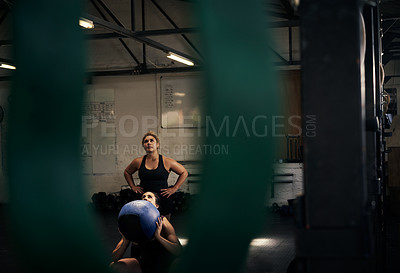Buy stock photo Cropped shot of an attractive young woman working out with her personal trainer in the gym