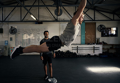Buy stock photo Full length shot of a handsome young man working out wth his personal trainer in the gym