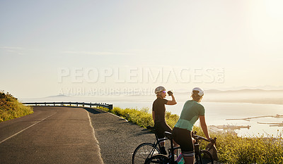 Buy stock photo Shot of two sporty young women admiring the view while out cycling