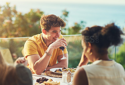 Buy stock photo Shot of a handsome young man enjoying a glass of wine while sitting around a table with friends outdoors
