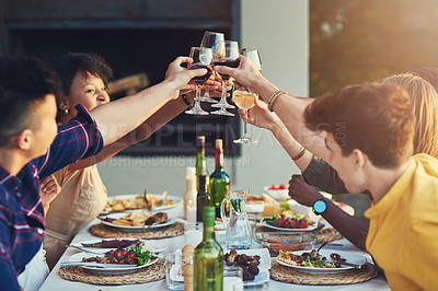 Buy stock photo Shot of a group of friends raising up their glasses for a toast while sitting around a table together outdoors
