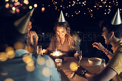 Buy stock photo Shot of a group of friends celebrating a birthday together around a table at a gathering outdoors in the evening