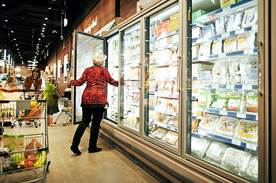 Buy stock photo Shot of a mature woman shopping in the cold produce section of a supermarket
