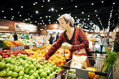 Buy stock photo Shot of a mature woman shopping for fresh produce at a supermarket