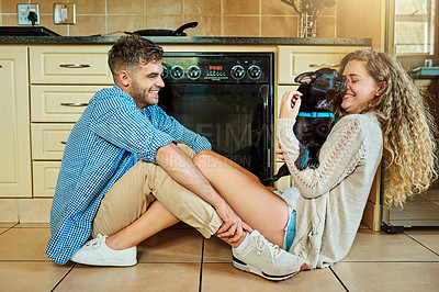 Buy stock photo Shot of a young couple spending time with their pup while sitting on their kitchen floor