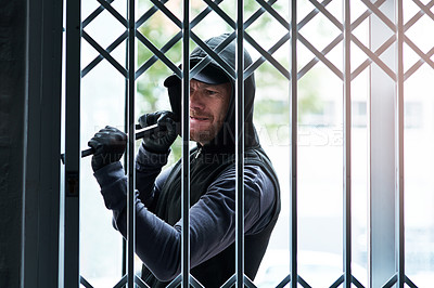 Buy stock photo Shot of a male burglar using a steel weapon to break into a house