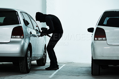 Buy stock photo Full length shot of a masked criminal picking the lock of a car door inside a parking lot