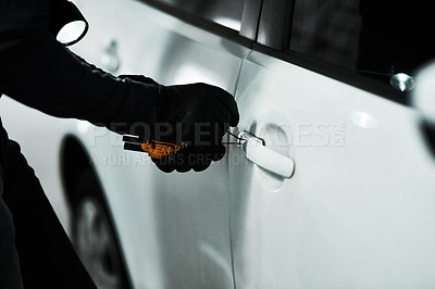 Buy stock photo Shot of an unrecognizable man picking the lock of a car inside a parking lot