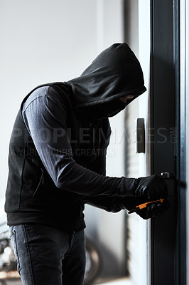 Buy stock photo Shot of a masked criminal busy picking the lock of a door in a garage